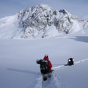 Hikers approaching a snowy peak